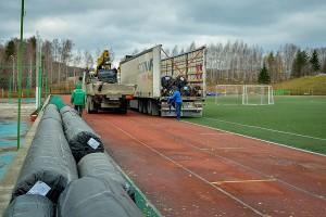 Разгрузка фур, доставивших в Кольцово новое покрытие для футбольного поля.